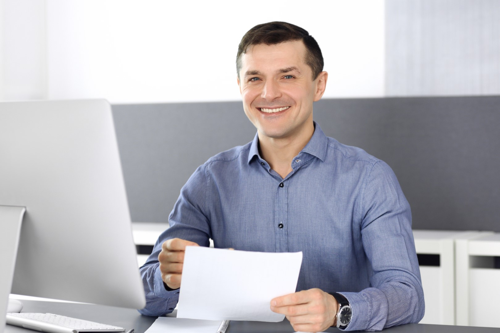 Man sitting at desk who could be a company director.